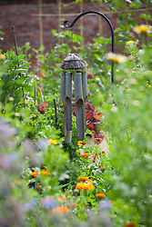 Wind chime used as bird scarer in a vegetable garden to protect crops in a vegetable garden