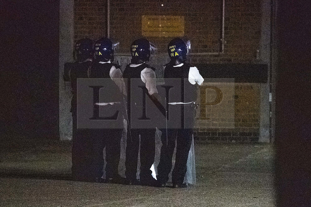 """© Licensed to London News Pictures. 21/07/2020. London, UK. Police wearing helmets and holding long riot shields stand and look on at the scene at the rear of the Southall Fire Station. A large scale emergency services operation underway while police are in a standoff with a person """"at height"""" close to the Southall Fire station. Photo credit: Peter Manning/LNP"""