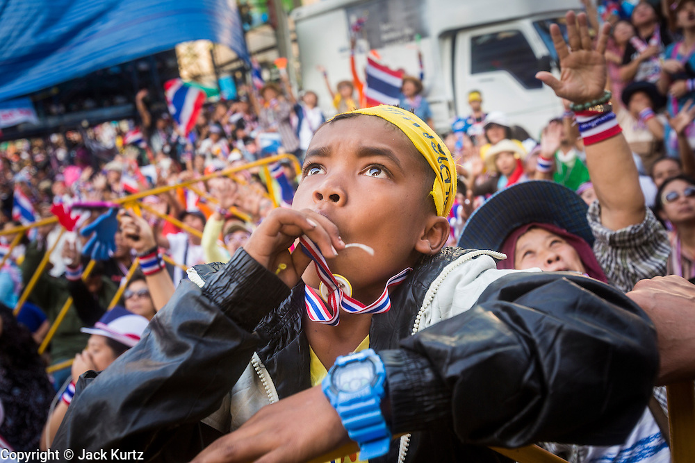 "13 JANUARY 2014 - BANGKOK, THAILAND: A Thai boy wearing a Long Live the King headband watches the stage during an anti-government protest in Bangkok. Tens of thousands of Thai anti-government protestors took to the streets of Bangkok Monday to shut down the Thai capitol. The protest was called ""Shutdown Bangkok"" and is expected to last at least a week. The Shutdown Bangkok protest is a continuation of protests that started in early November. There have been shootings almost every night at different protests sites around Bangkok, including two Sunday night, but the protests Monday were peaceful. The malls in Bangkok stayed open Monday but many other businesses closed for the day and mass transit was swamped with both protestors and people who had to use mass transit because the roads were blocked.    PHOTO BY JACK KURTZ"