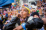 """13 JANUARY 2014 - BANGKOK, THAILAND: A Thai boy wearing a Long Live the King headband watches the stage during an anti-government protest in Bangkok. Tens of thousands of Thai anti-government protestors took to the streets of Bangkok Monday to shut down the Thai capitol. The protest was called """"Shutdown Bangkok"""" and is expected to last at least a week. The Shutdown Bangkok protest is a continuation of protests that started in early November. There have been shootings almost every night at different protests sites around Bangkok, including two Sunday night, but the protests Monday were peaceful. The malls in Bangkok stayed open Monday but many other businesses closed for the day and mass transit was swamped with both protestors and people who had to use mass transit because the roads were blocked.    PHOTO BY JACK KURTZ"""