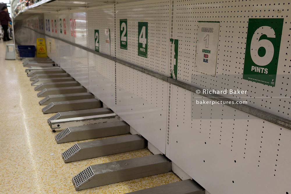 As the UK government announces further Coronavirus-related restrictions to its citizens, with the immediate closure of pubs, cafes, gyms and cinemas, and the worldwide number of deaths reaching 10,000 with 240,000 cases, 953 of those in London alone, there are empty spaces where milk was sold at a Sainsbury's supermarket in East Dulwich, on 20th March 2020, in London, England.