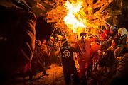 Group of people burning wooden structure at night, Nozawaonsen, Japan