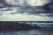 Man standing on wave breaker looking into the distance