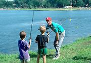 Volunteer teaching fishing skills to kids at Lake Calhoun age 36 and 6.  Minneapolis Minnesota USA