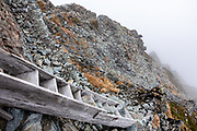 """Seen here in the fog, the infamous Daikiretto Gap, secured by chains and ladders, is one of the most difficult non-technical routes in Japan. Kita-hotaka Mountain Hut perches near the summit of Mount Kitahotaka, which reaches 3106 m elevation (10,190 ft, Japan's 9th highest) in Chubu-Sangaku National Park, Japan. This is the highest hut in Japan, excluding those on Mt Fuji. I hiked Kitahotaka (or Kitahotaka-dake) 4km round trip from Karasawa Goya hut via a steep trail secured with chains & ladders ascending 800 meters. Mt Kitahotaka is the second highest peak on Mount Hotaka (Hotaka-dake or the Hotaka Mountains), which are in the """"Northern Japan Alps"""" (Hida Mountains). North of Kitahotaka-dake lies an exposed 3.5+ hour scramble via Daikiretto Gap helped by chains and ladders, connecting with Minamidake Mountain Hut. I avoided the Daikiretto by returning to Karasawa cirque, then walking all the way back to a comfortable dorm slot reserved at Tokusawa-en backcountry lodge (16 km, 800 meters up, 1615 m down)."""