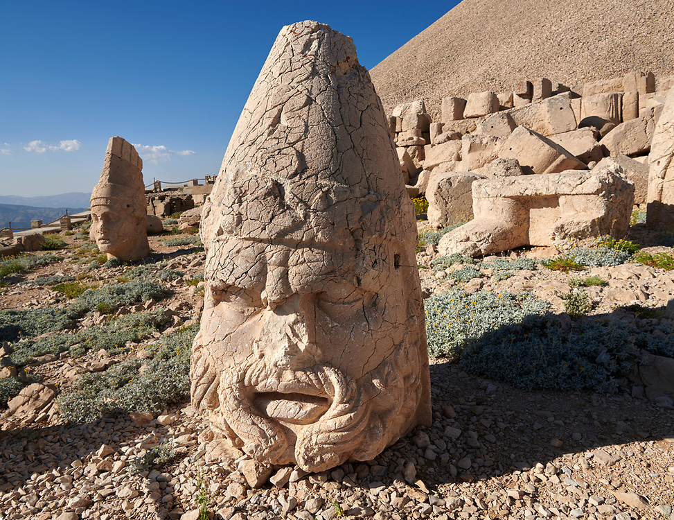 Statue head of Zeus & Antiocchus behind, in front of the 62 BC Royal Tomb of King Antiochus I Theos of Commagene, west Terrace, Mount Nemrut or Nemrud Dagi summit, near Adıyaman, Turkey .<br /> <br /> If you prefer to buy from our ALAMY PHOTO LIBRARY  Collection visit : https://www.alamy.com/portfolio/paul-williams-funkystock/nemrutdagiancientstatues-turkey.html<br /> <br /> Visit our CLASSICAL WORLD HISTORIC SITES PHOTO COLLECTIONS for more photos to download or buy as wall art prints https://funkystock.photoshelter.com/gallery-collection/Classical-Era-Historic-Sites-Archaeological-Sites-Pictures-Images/C0000g4bSGiDL9rw