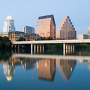 Austin skyline in the twilight with several tall modern buildings in downtown Austin reflected on Town Lake. In the middle of the frame is the Congress Avenue Bridge. The shot is taken from the southern bank of Town Lake facing east.