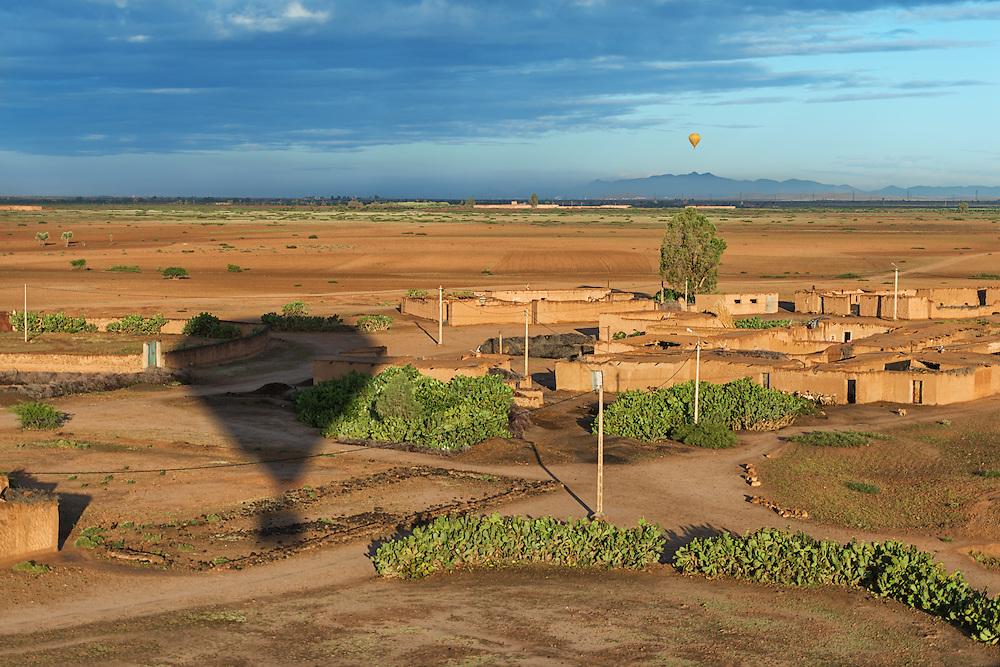Hot-air balloon shadow over rural Marrakech, Morocco.