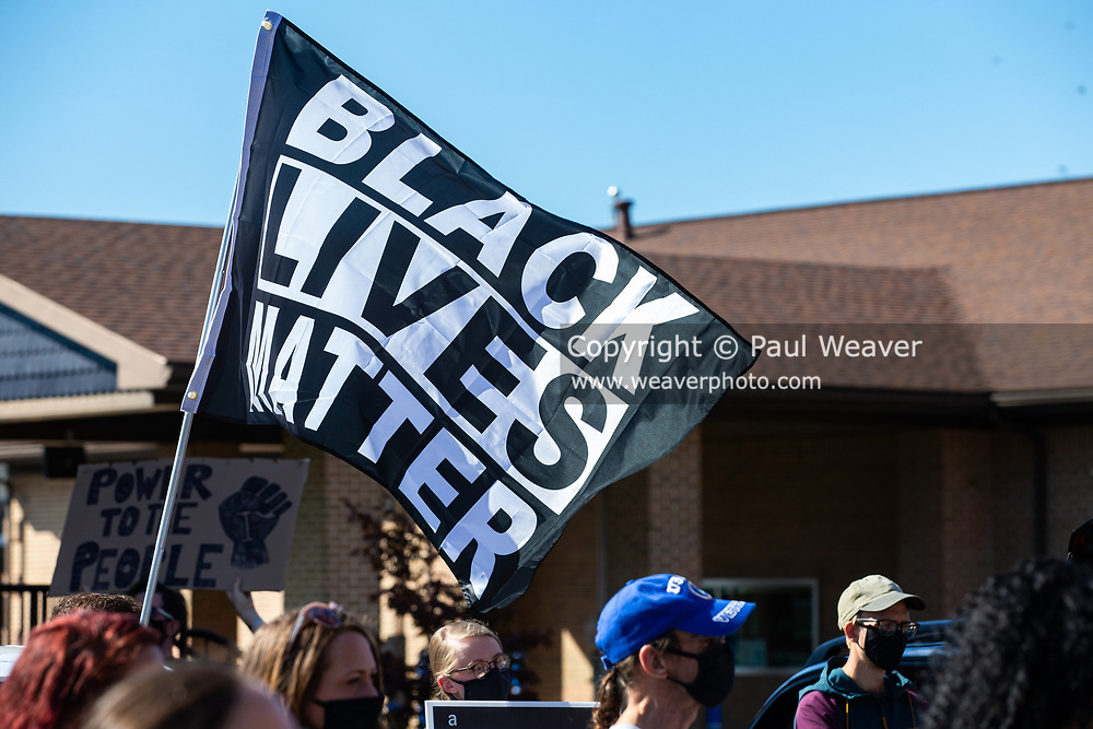 A protester holds a Black Lives Matter flag at a rally outside of the police station in Milton, Pennsylvania.