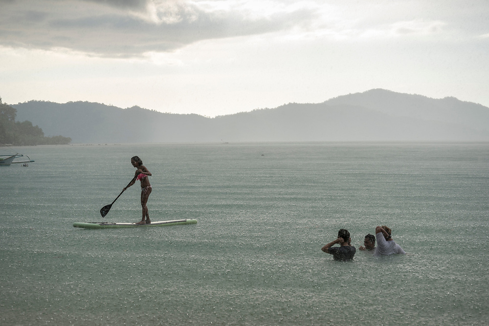 Port Barton, Palawan, Philippines - July 8, 2019:  A late afternoon rain splatters the sea as a group of men swim and a woman maneuvers a stand-up paddle board in Port Barton.