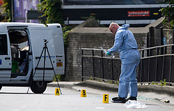 © Licensed to London News Pictures. 07/07/2016. London, UK. A police forensics officer gathering evidence at the scene where a man was struck by a car following an assault on Harrow Road in Harlesden, north west London. Photo credit: Ben Cawthra/LNP