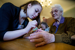 Elderly woman having her nails painted, residential home for the elderly UK