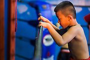 23 DECEMBER 2014 - BANGKOK, THAILAND: A child who hopes to box warms up at the ropes in the ring at the Kanisorn gym in Bangkok. The Kanisorn boxing gym is a small gym along the Wong Wian Yai - Samut Sakhon train tracks. Young people from the nearby communities come to the gym to learn Thai boxing. Muay Thai (Muai Thai) is a mixed martial art developed in Thailand. Muay Thai became widespread internationally in the twentieth century, when Thai boxers defeated other well known boxers. A professional league is governed by the World Muay Thai Council. Muay Thai is frequently seen as a way out of poverty for young Thais. Muay Thai professionals and champions are often celebrities in Thailand.     PHOTO BY JACK KURTZ