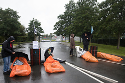 Farnborough, UK. 2nd October, 2021. Extinction Rebellion climate activists lie in the road locked to fuel barrels in order to block an entrance to Farnborough Airport. The activists blocked three entrances to the private airport to highlight elevated carbon dioxide levels produced by super-rich passengers using private jets and 'greenwashing' by the airport in announcing a switch to sustainable aviation fuel (SAF).
