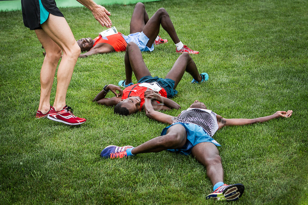 Winner Bedan Karoki of Kenya lays on the ground with fellow African runners after finishing the Beach to Beacon 10K road race in Cape Elizabeth, Maine. Local running star Ben True helps after finishing third