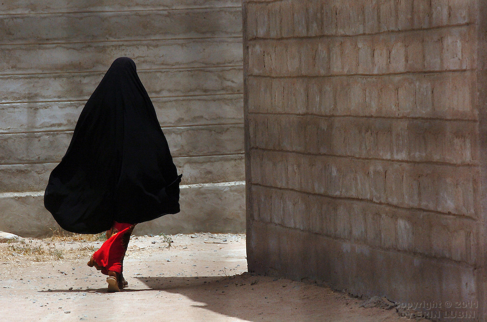A woman rounds a corner at the secondary school in Ifo Refugee Camp, Dadaab, Kenya.September 12, 2006. ..Photograph by Erin Lubin