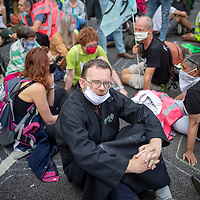 Fr Martin Newell sits during a mass civil disobedience action in Parliament Square, protests that urged the government to take action on climate change. Fr Newell was arrested later in the day.