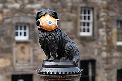 Edinburgh, Scotland, UK. 24 March, 2020.  Deserted streets in the heart of the Old Town tourist district in Edinburgh. All shops and restaurants are closed with very few people venturing outside following the Government imposed lockdown today. Pictured; Famous Greyfriars Bobby statue of dog wearing a face mask. Iain Masterton/Alamy Live News