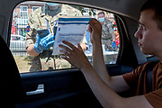 A young man in his twenties shows his completed sample to army personnel from the rear seat of a car after a self-administered Coronavirus (COVID-19) test (inserting a swab into the nose and throat) in south London. There are four steps to the self-administered Covid-19 test which the public works through in their car, and with communications with army personnel via phone or through closed windows, in a south London leisure centre, on 2nd June 2020, in London, England. The kit provided consists of a booklet, plastic bag, swab, vial, bar codes and a sealable biohazard bag. The swab sample is taken from the back of the throat and nasal passage with the contents sealed and returned to soldiers through a narrow window. The whole process takes between 5-10mins with results available with 48hrs.