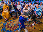 15 DECEMBER 2013 - BANGKOK, THAILAND:    Members of the public sit in the lobby of the Queen Sirikit Convention Center and listen to speakers during a forum on political reform in Thailand. The forum was organized by Thai Prime Minister Yingluck Shinawatra.      PHOTO BY JACK KURTZ