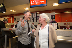 Alan Cumming with -assenger Christine Gardiner, at the checkin gate, as Delta launch their new year-round nonstop service from Edinburgh to New York-JFK today at Edinburgh Airport.