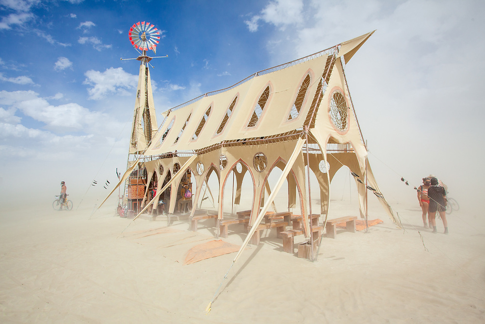 Prairie Wind Chapel from: Venice, CA year: 2015<br /> <br /> Excavated from a dust bowl near the border of Oklahoma and Saskatchewan, the Prairie Wind Chapel was once the heart of the roving town of Aeolia until a tornado wiped it all from the map. As the sole remaining structure of this ghost town, the chapel captures the pilgrims' peculiar affinity for worshiping the wind and the beautiful mysteries this silent force creates on the open plain. Twin copper wind harps flank the canvas chapel, enticing lost travelers with a dreamy siren song. Towering over the altar is a 40 ft. steel windmill which pumps a Victorian reed organ and two wood and metal pipe organs. Evoking the melancholic demise of the wind worshiping Aeolians, modern pilgrims can play three wind-powered keyboards, filling the restored chapel with the ephemeral sounds of yesterday. The Prairie Wind Chapel welcomes all wayfarers with its songs! URL: https://www.facebook.com/WindSoundSanctuary