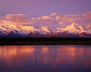 Mt. Mather, 12,123 feet, and Mt. Brooks, 11,940 feet, illuminated at sunrise and reflected in tundra pond, Denali National Park, Alaska.