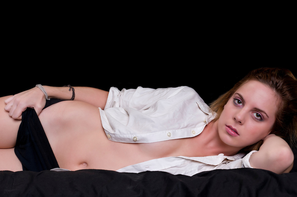 Portrait of sensual woman with shirt in bed looking at camera.