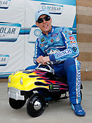 Kevin Harvick sits on his NASCAR Cup Series pole award at the Kansas Speedway in Kansas City, Kan., Friday, May 11, 2018. (AP Photo/Colin E. Braley)