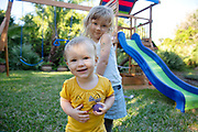 2 kids playing in the backyard together outside by play structure having fun looking at camera