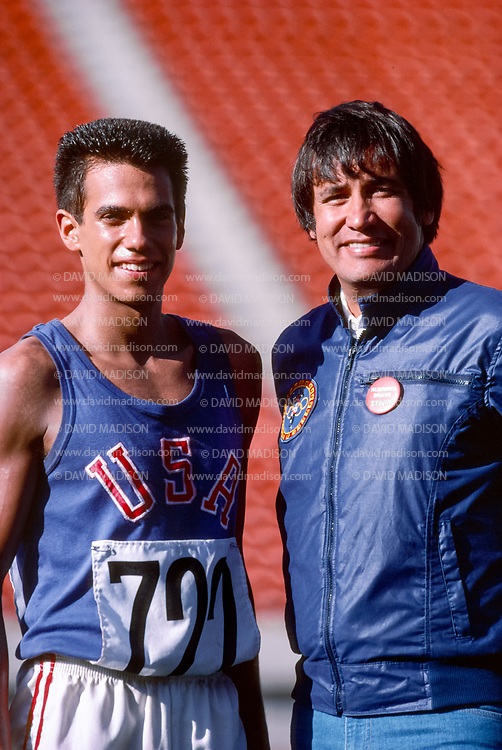 EDMONTON, CANADA - OCTOBER 11:  Actor Robby Benson #722 of the USA (left) stands with Billy Mills of the USA (RIGHT) during production of the movie Running Brave filmed in Commonwealth Stadium in Edmonton, Canada in this photograph taken October 11, 1982.  The movie recreates Billy Mills' historic win in the 1964 Olympic Games 10000 meter race.  (Photo by David Madison/Getty Images)