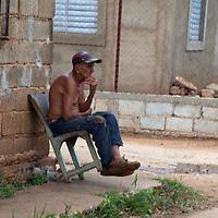 Central America, Cuba, Remedios. Cuban man leans back in chair on corner.