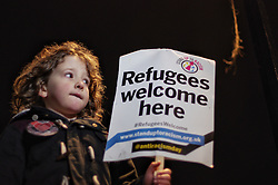 © Licensed to London News Pictures. 22/02/2016. London, UK. A child holds a banner at a 'Refugees Welcome' demonstration on Whitehall, opposite Downing Street this evening (22/02/2016). A large part of the Calais refugee camp, referred to as The Jungle, has been give an eviction notice by French courts.  Photo credit: Denis McWilliams/LNP