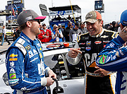 Dale Earnhardt Jr., left, and Ryan Newman, right, visit before the start of a NASCAR Cup Series auto race at Kansas Speedway in Kansas City, Kan., Sunday, Oct. 22, 2017. (AP Photo/Colin E. Braley)