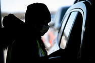 A vaccine administrator stands by a car as Lehigh Valley Health Network holds a COVID-19 mass vaccination clinic Mar. 20, 2021, at Pocono Raceway in Long Pond, Pennsylvania. Administrators were expected to vaccinate 3,000 people in the state of Pennsylvania's Phase 1A with the Moderna vaccine.