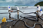 30 JULY 2013 - KOH SAMET, RAYONG, THAILAND: Workers carry hoses out to the surf during cleanup of an oil spill on Ao Prao beach on Koh Samet island. About 50,000 liters of crude oil poured out of a pipeline in the Gulf of Thailand over the weekend authorities said. The oil made landfall on the white sand beaches of Ao Prao, on Koh Samet, a popular tourists destination in Rayong province about 2.5 hours southeast of Bangkok. Workers from PTT Global, owner of the pipeline, and up to 500 Thai military personnel are cleaning up the beaches. Tourists staying near the spill, which fouled Ao Prao beach, were evacuated to hotels on the east side of the island, which was not impacted by the spill. PTT Global Chemical Pcl is part of state-controlled PTT Pcl, Thailand's biggest energy firm.      PHOTO BY JACK KURTZ