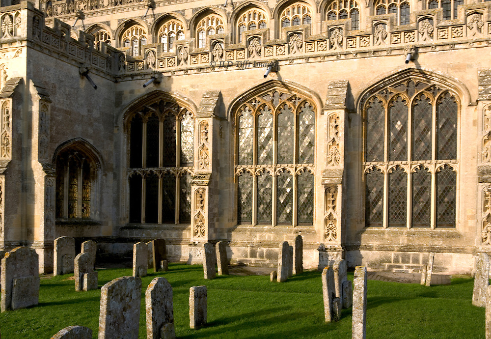 South facade of St. Peter and St. Paul wool church in Lavenham, seen from near the south entrance.  A few gravestones scattered close to the church, casting shadows.  The late afternoon sun reflected off the 8-light Late Perpendicular style windows of the church.  Finely carved ornament on the buttresses and along the roof.