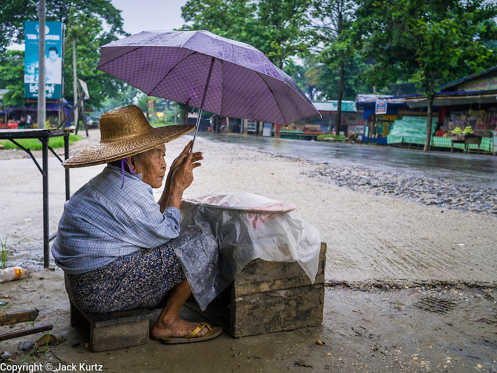 14 JUNE 2013 -  SAMALAUK, AYEYARWADY, MYANMAR:  A Woman sits under an umbrella in the rain along Highway 5 in Samalauk, Ayeyarwady, in the Irrawaddy delta region of Myanmar. Most Burmese men join the clergy at least once in the lives, sometimes for just a few weeks, other times for a lifetime commitment. This region of Myanmar was devastated by cyclone Nargis in 2008 but daily life has resumed and it is now a leading rice producing region.  PHOTO BY JACK KURTZ
