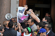 © licensed to London News Pictures. LONDON, UK.  09/08/11. Crowds tear a photograph of  Muammar Gaddafi with an expiry date written over it. The flag is changed at the Libyan Embassy in London. Diplomats named by Libya's rebel administration, the National Transitional Council (NTC), took over the London embassy today (Tues 9th August 2011) previously staffed by appointees of Muammar Gaddafi's government Mandatory Credit Stephen Simpson/LNP