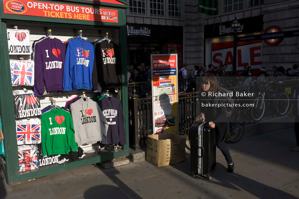 Visitor pushes wheeled suitcase through Piccadilly Circus, past a tourist souvenir kiosk selling 'I Love London' hoodies.