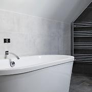 Freestanding bath in a black and white bathroom.