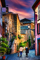 """""""An evening stroll on the ancient cobbled streets of Orvieto""""… <br /> <br /> Orvieto is one of the most striking, memorable, and enjoyable hill towns in central Italy. Less than 90 minutes from Rome, Orvieto sits majestically high above the valley floor atop a big chunk of volcanic stone called tufa and overlooking cypress-dotted Umbrian plains and vineyards. The ancient city rewards one with a peaceful and historical stroll back in time to the days of the Etruscans, who built this clifftop village over 2000 years ago for protection from their enemies. The ancient Etruscan wall still stands today presenting colorful cliffside views, and protecting the famous Duomo di Orvieto, the Palazzo del Popolo, and other antique treasures. The blue evening skies reflect on the shiny-worn cobblestone Strada below as the last bit of sun illuminates the way for a delightful promenade. """"As sorrowful yet always rejoicing; as poor yet enriching many; as having nothing and yet possessing all things.""""  <br /> 2 Corinthians 6:10"""
