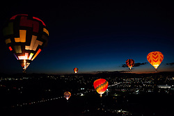 """""""Dawn Patrol 9"""" - Photograph of glowing hot air balloons flying for the Dawn Patrol at the 2012 Great Reno Balloon Race. Photographed from a hot air balloon."""