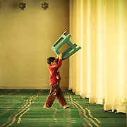 A small boy re-arranges the furniture at al-Hakim Mosque in Old Cairo, Egypt.
