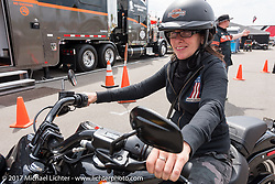 A German woman getting back from a test ride of a new 2017 Harley at the Harley-Davidson display at the Daytona International Speedway during Daytona Beach Bike Week. FL. USA. Sunday March 12, 2017. Photography ©2017 Michael Lichter.