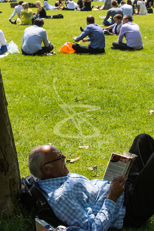 Green Park, London, June 6th 2016. A man relaxes with a book in the shade in Green Park as London basks in glorious summer sunshine with highs of 24º expected.