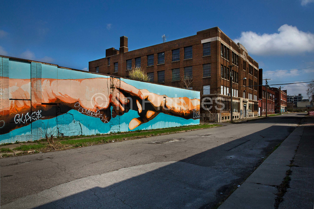 """Mural as a homage to Michaelangelo's Sistine Chapel in Rome painted on Grand Boulevard Detroit. Known as the world's traditional automotive center, """"Detroit"""" is a metonym for the American automobile industry and an important source of popular music legacies celebrated by the city's two familiar nicknames, the Motor City and Motown. Many neighborhoods remain distressed since the collapse of the motor industry. The state governor declared a financial emergency in March 2013, appointing an emergency manager. On July 18, 2013, Detroit filed the largest municipal bankruptcy case in U.S. history."""