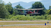 New Standard biplane landing at Wings and Wheels.