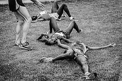 Beach to Beacon 10K: Ben True comes to help runners laying on grass after finish, Stephen Kibet, winner Bedan Karoki, Patrick Makau, all of Kenya