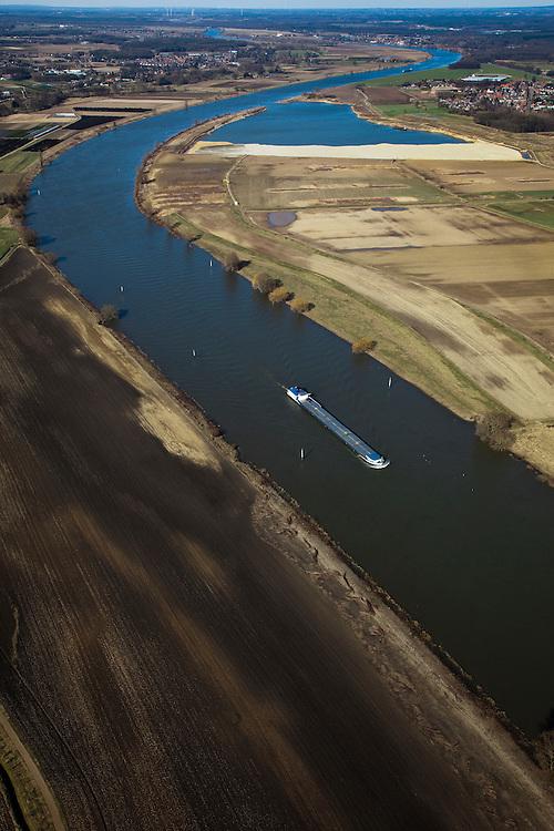 Nederland, Limburg, Gemeente Venlo, 07-03-2010; Binnenvaartschip op de Maas ter hoogte van Lomm (voormalige gemeente Arcen en Velden). Hoogwatergeul in wording in het kader van bescherming tegen hoogwater. De geul zal in de komende jaren verder uitgegraven worden in het gebied rechts van de Maas (oostelijk) met als gevolg lagere waterstanden (ter plaatse, en stroomopwaarts). In het gebied onstaat verder nieuwe 'natte' natuur.  Foto in noordelijke richting..Lomm, flood channel in the making in the context of flood protection. The channel will be further excavated in the coming years in the area right of the river Meuse, resulting in lower water levels (on site and upstream). The area will become new 'wet' nature..luchtfoto (toeslag), aerial photo (additional fee required).foto/photo Siebe Swart.